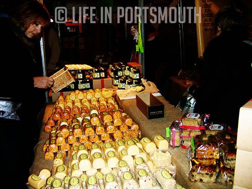 Venta de quesos artesanales en un puesto del mercado navideño.